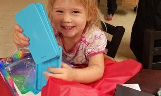 Little girl opening her birthday present