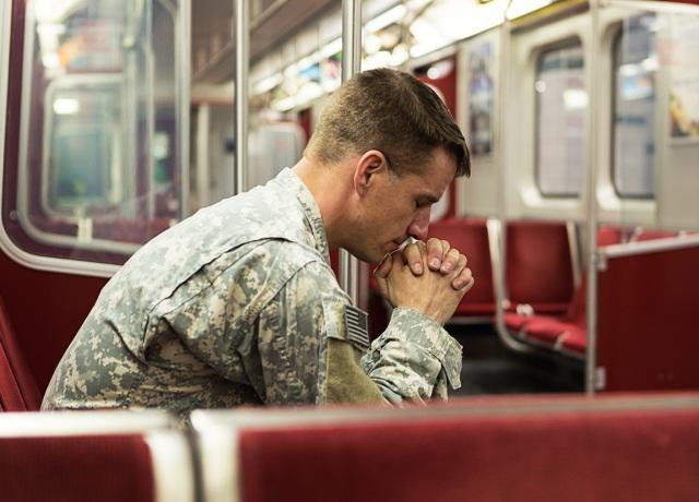 Soldier praying on a train - small