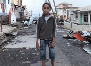 A child standing in the aftermath of Hurricane Maria in Puerto Rico