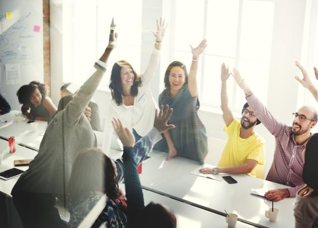 Happy employees around a conference table - sml