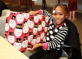 Girl at Theodora House receiving a Christmas gift