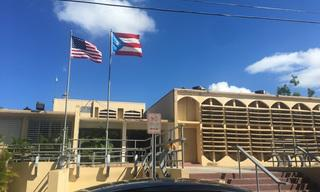 U.S. and PR flags in front of a building