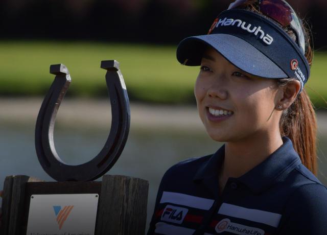 Winning LPGA golfer accepting trophy at sponsor event