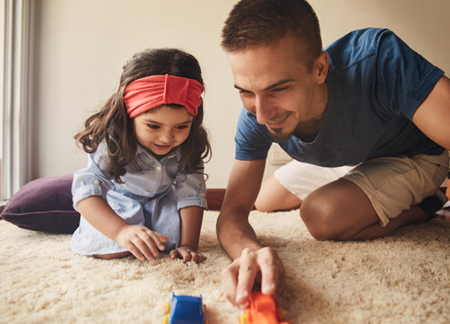 Dad and little girl playing on the floor with toy cars