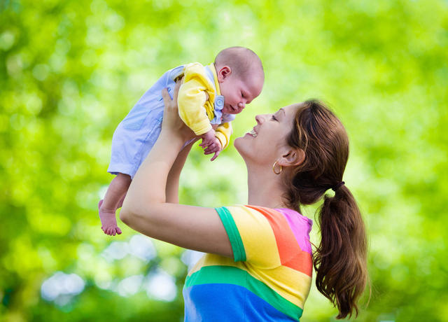 Mom holding baby into the air smiling with green trees in the background
