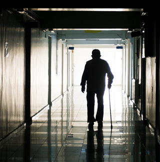 Elderly Man walking down hallway