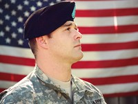 man-wearing-combat-hat-and-top-looking-up-near-flag-of-1202726.jpg