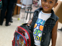 Boy with donated backpack from Operation Backpack