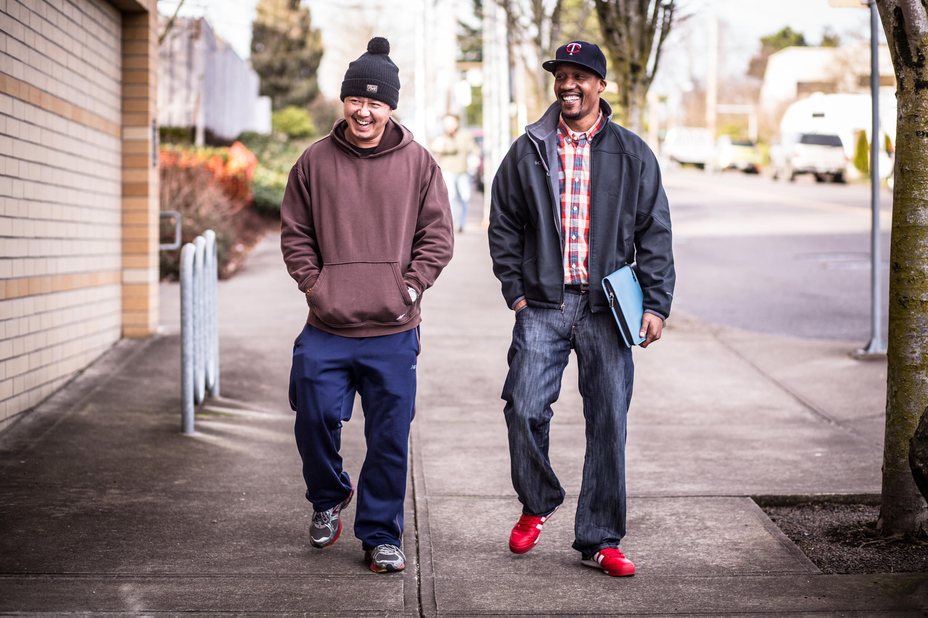 Two men walking down a sidewalk smiling