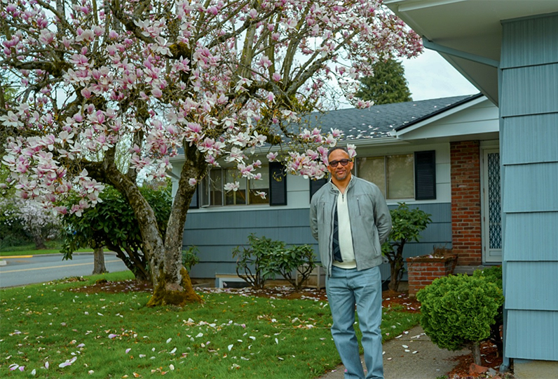 Man standing in front of the Harry Watson house