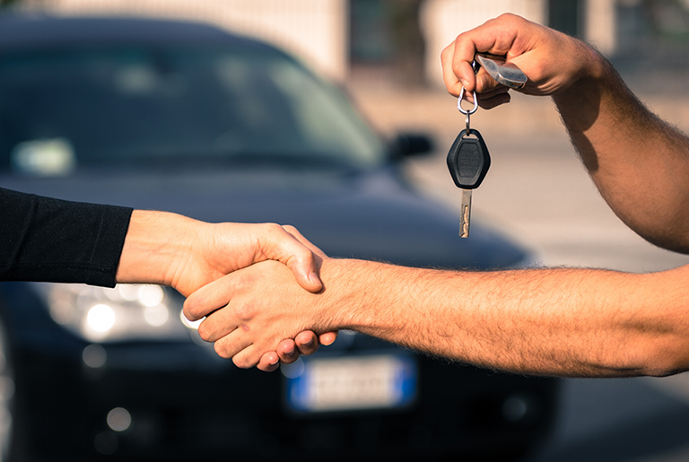 People shaking hands, one person is holding car keys