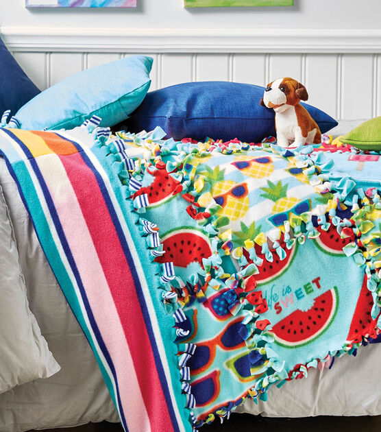 Colorful no-sew quilt laying on white bed. A teal and blue pillow are on top of the quilt.